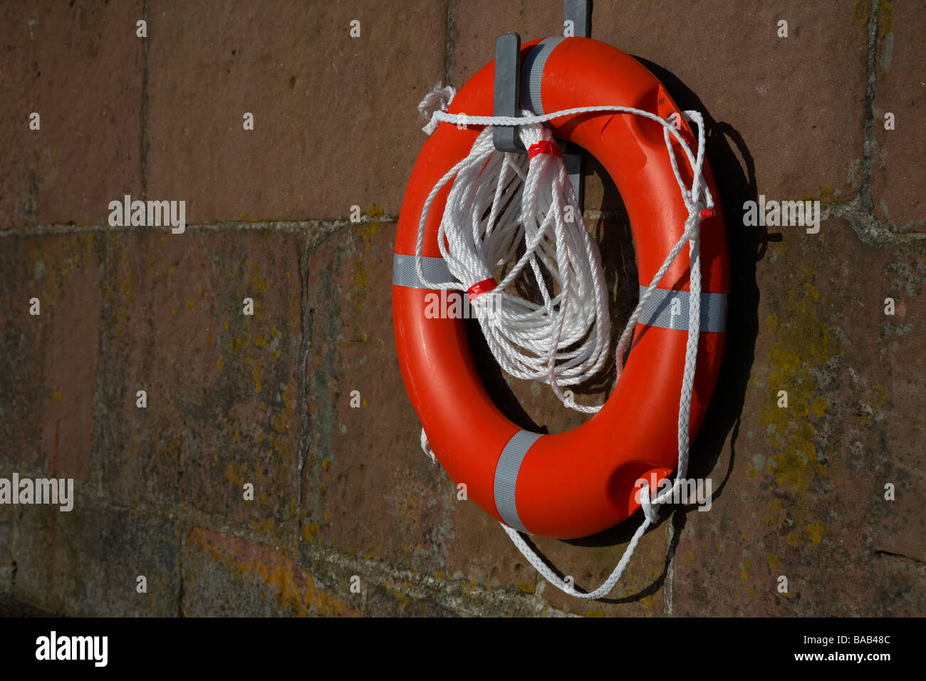 brand new bright red lifebelt with white rope hanging on a hanger on brown harbour wall - Stock Image