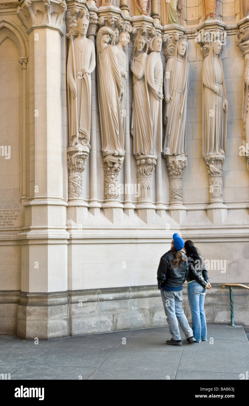 Visitors admiring sculptures on the facade of the Cathedral of St. John the Divine in New York CIty - Stock Image