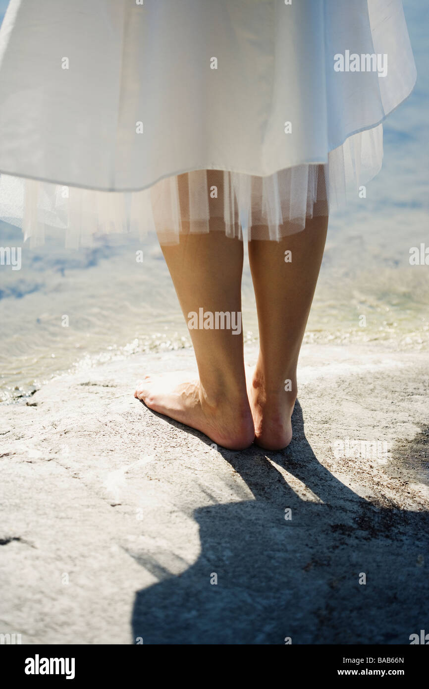 Barefooted bride on a cliff by the water, Sweden. - Stock Image