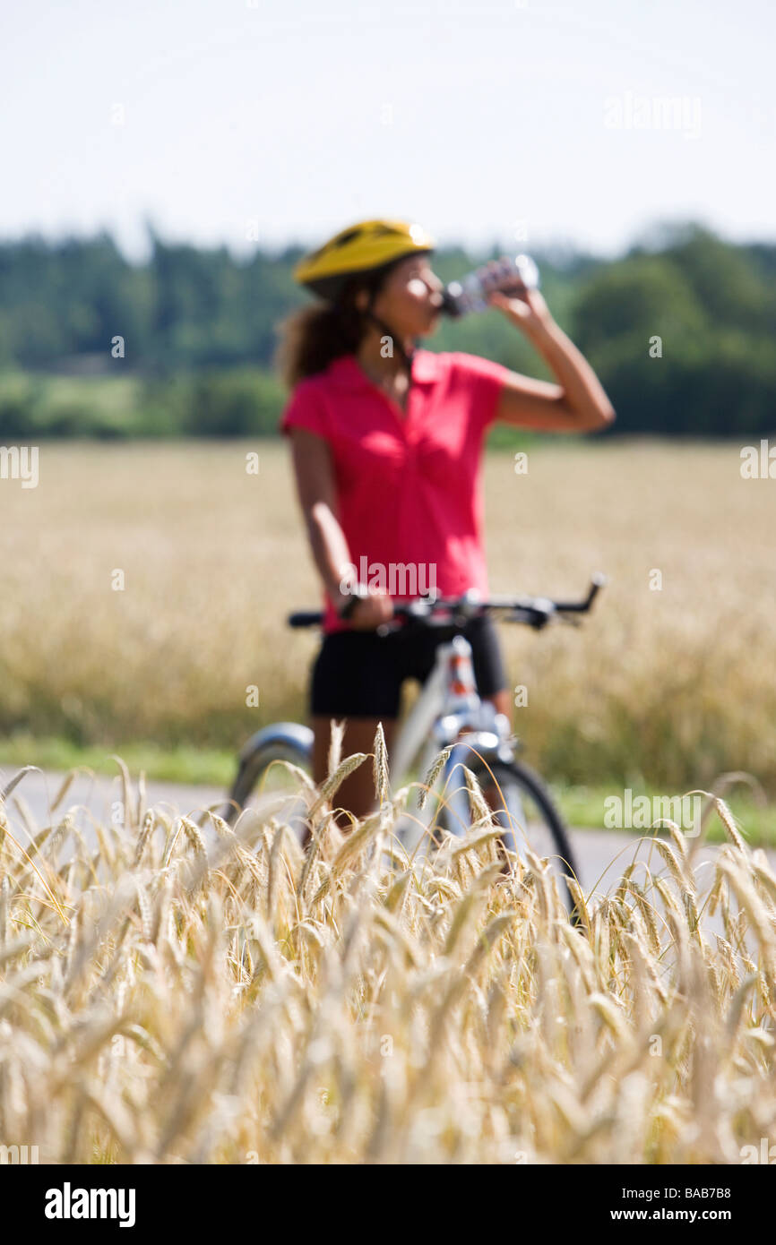 A woman riding a bike and drinking water in the countryside, Sweden. - Stock Image