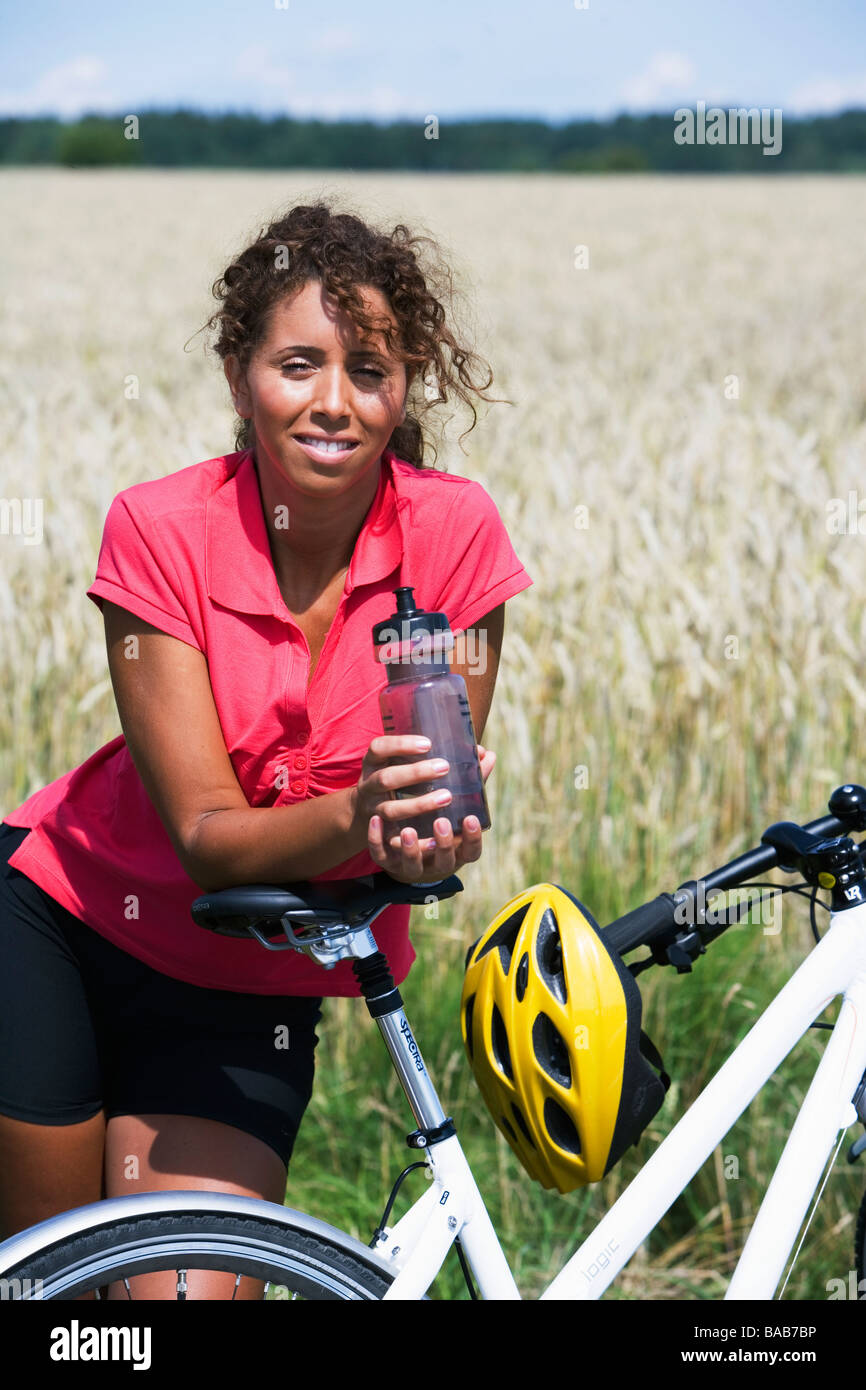 A woman with a water bottle and a bicycle, Sweden. - Stock Image