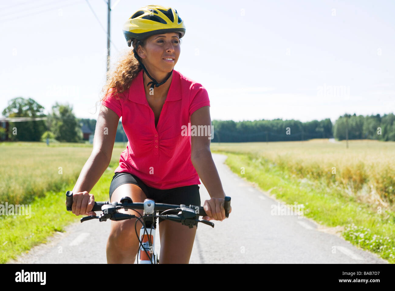 A woman riding a bike in the countryside, Sweden. - Stock Image