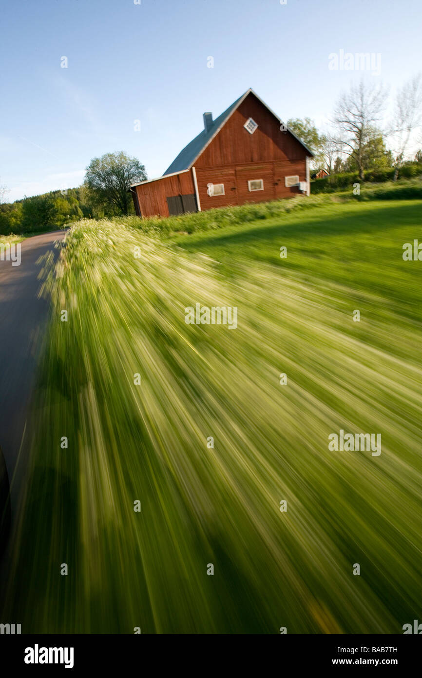 Field and a barn blurry motion Sweden. - Stock Image