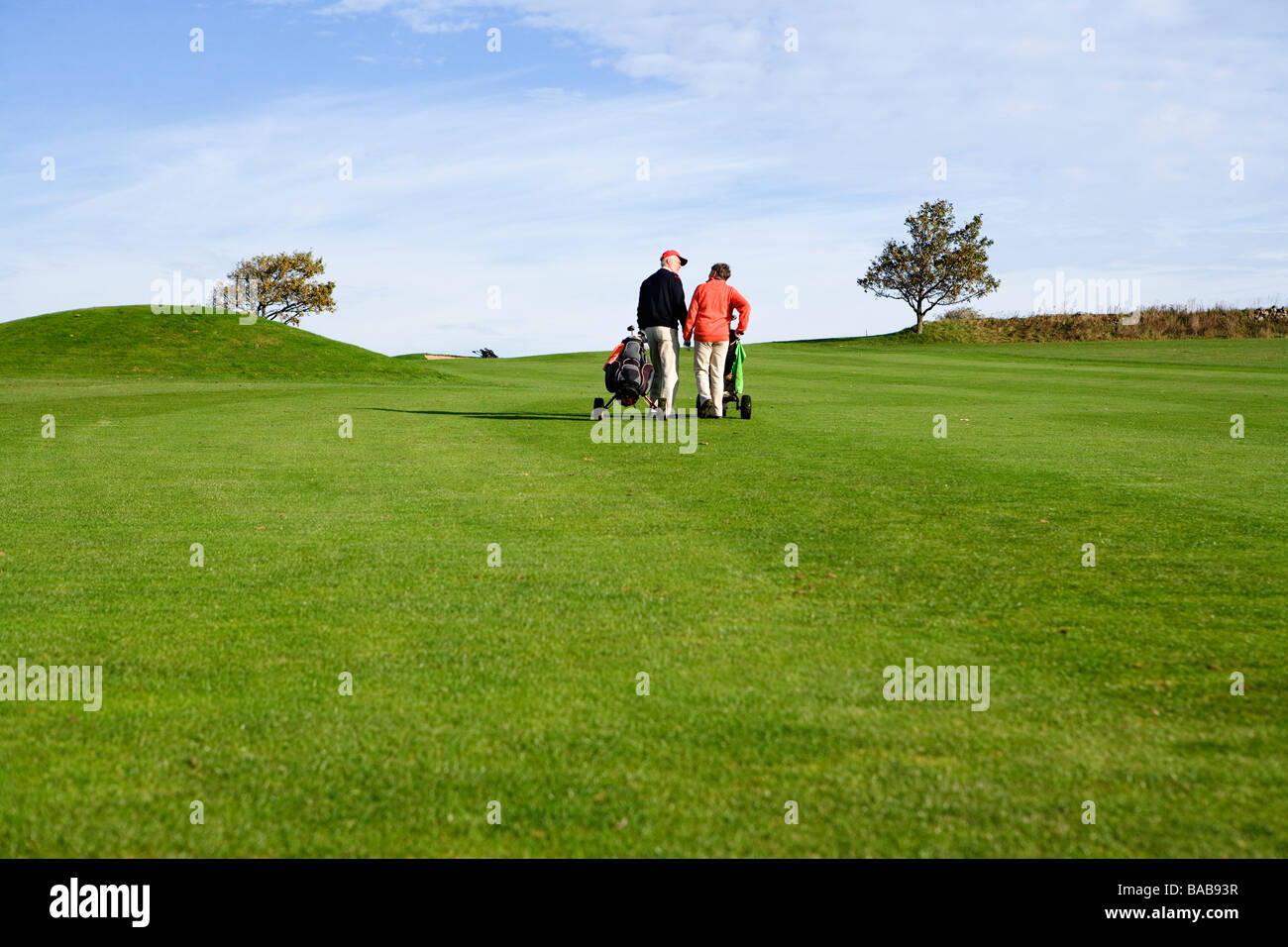 An elderly couple playing golf Skane Sweden. - Stock Image