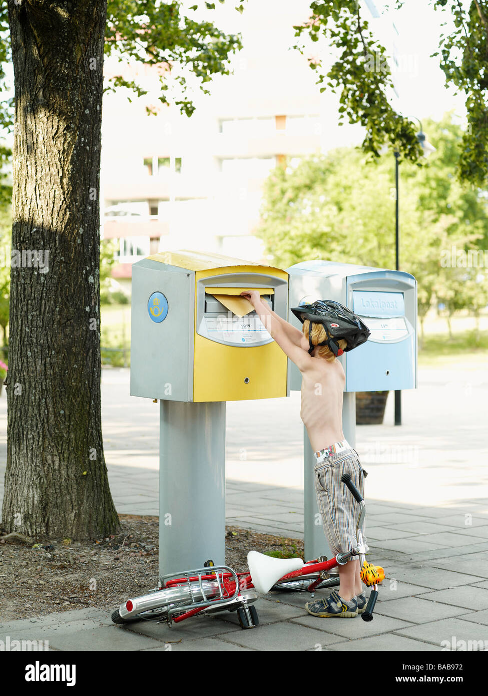 A boy dropping a letter into a box Sweden. - Stock Image