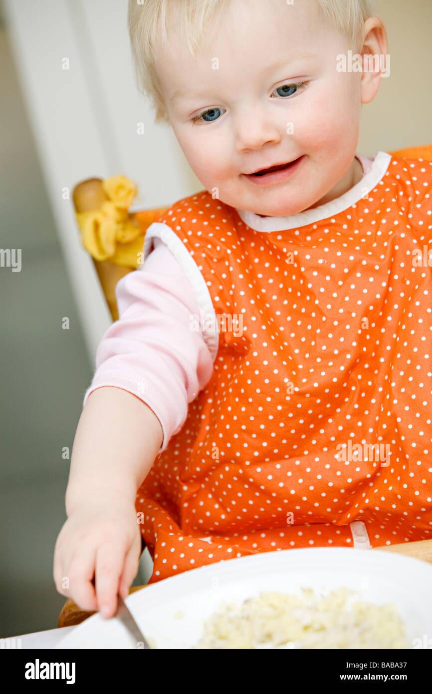 Blond baby girl eating Sweden. - Stock Image