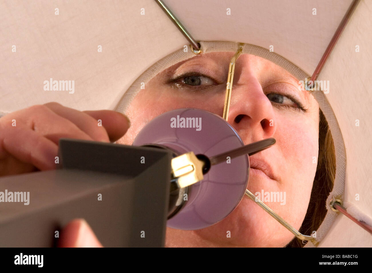 A close up of a woman reaching into a lamp to turn it on. - Stock Image