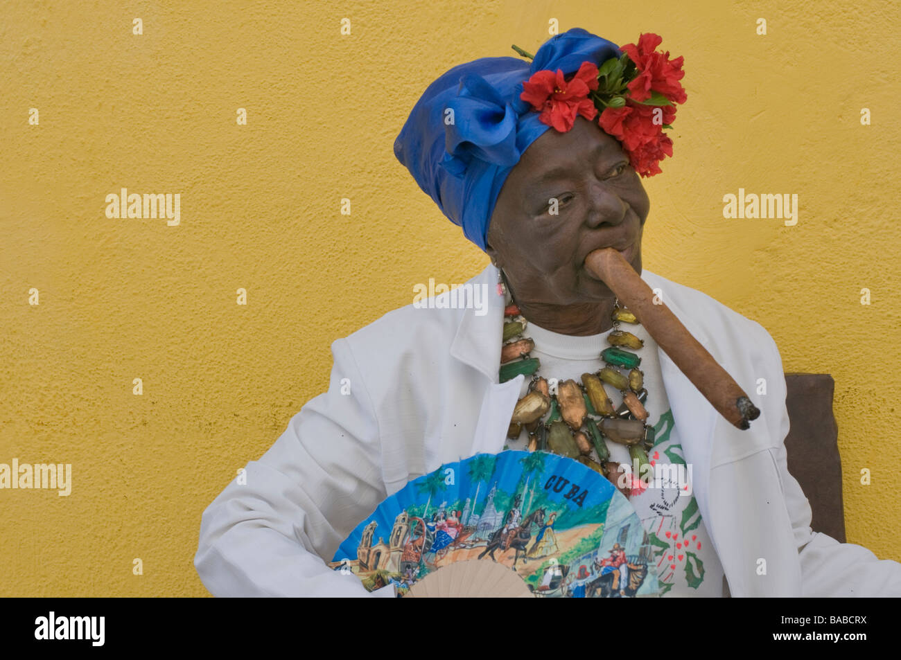 Older woman smoking a large cigar dressed in the white of Santeria with a headdress and flowers as well as a fan. - Stock Image