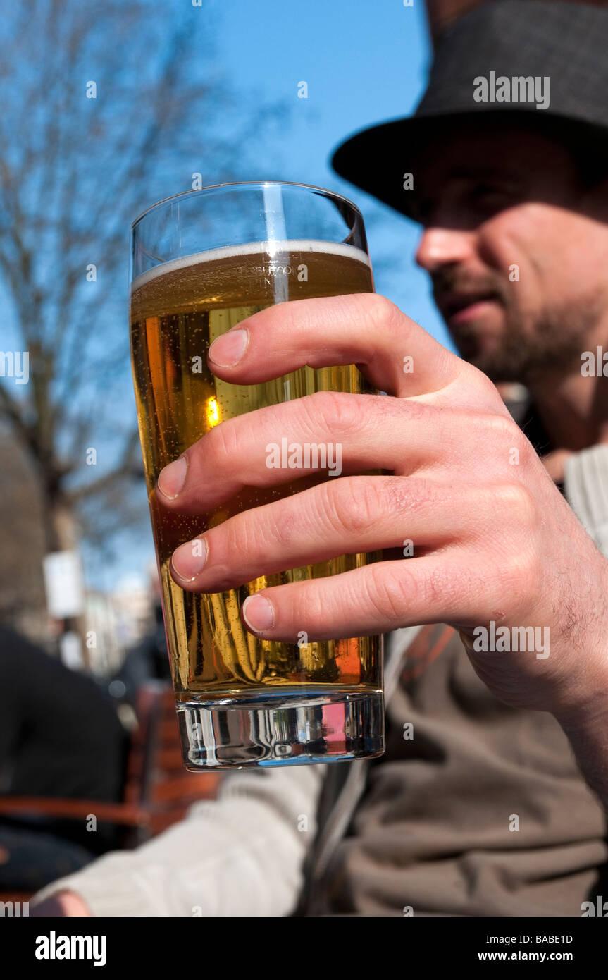 Man drinking pint of lager outside pub UK - Stock Image