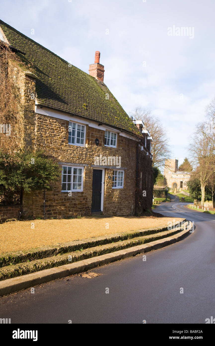 Main street with cottages and village church Scaldwell Northamptonshire England UK GB - Stock Image