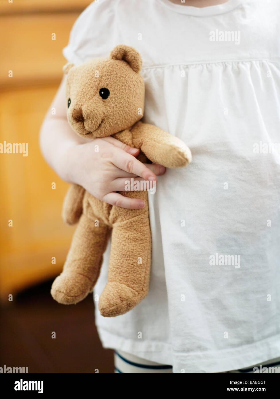 A girl holding a teddybear - Stock Image