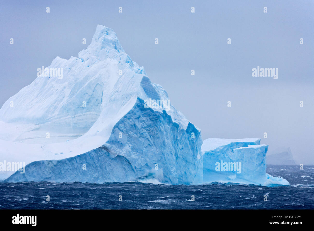 Blue iceberg in stormy seas Weddell Sea Antarctica - Stock Image