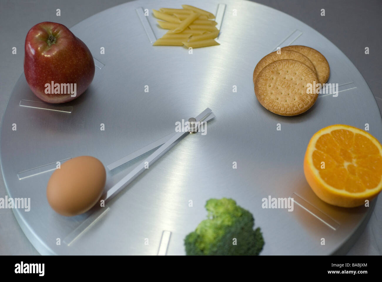 clock food control- pasta, biscuits, orange, apple, egg and broccoli - Stock Image