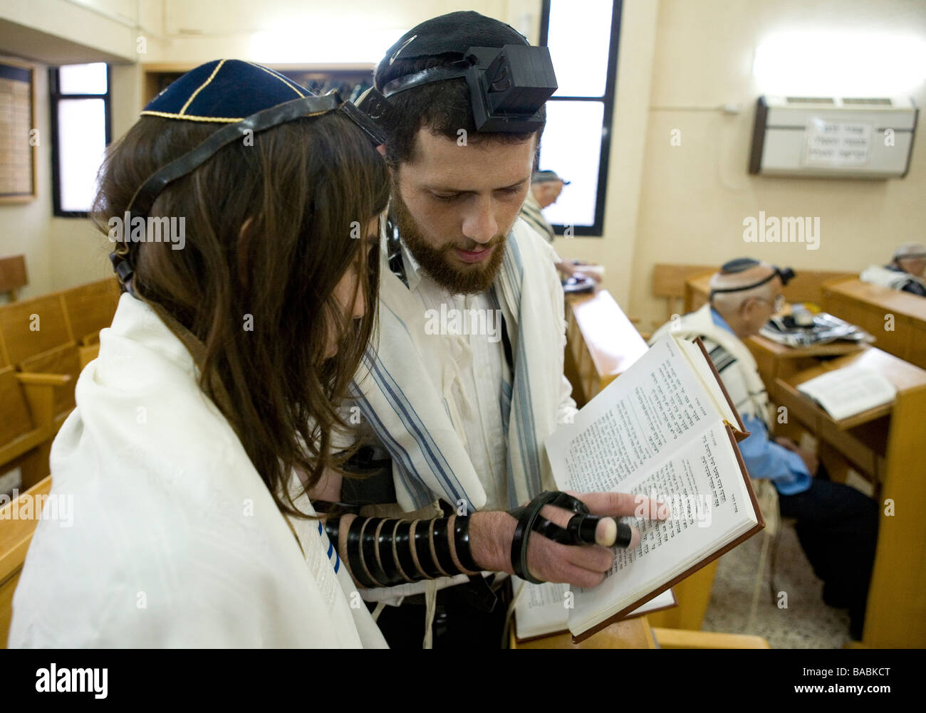 Bar Mitzvah ceremony in a synagogue Instructor teaching the service - Stock Image