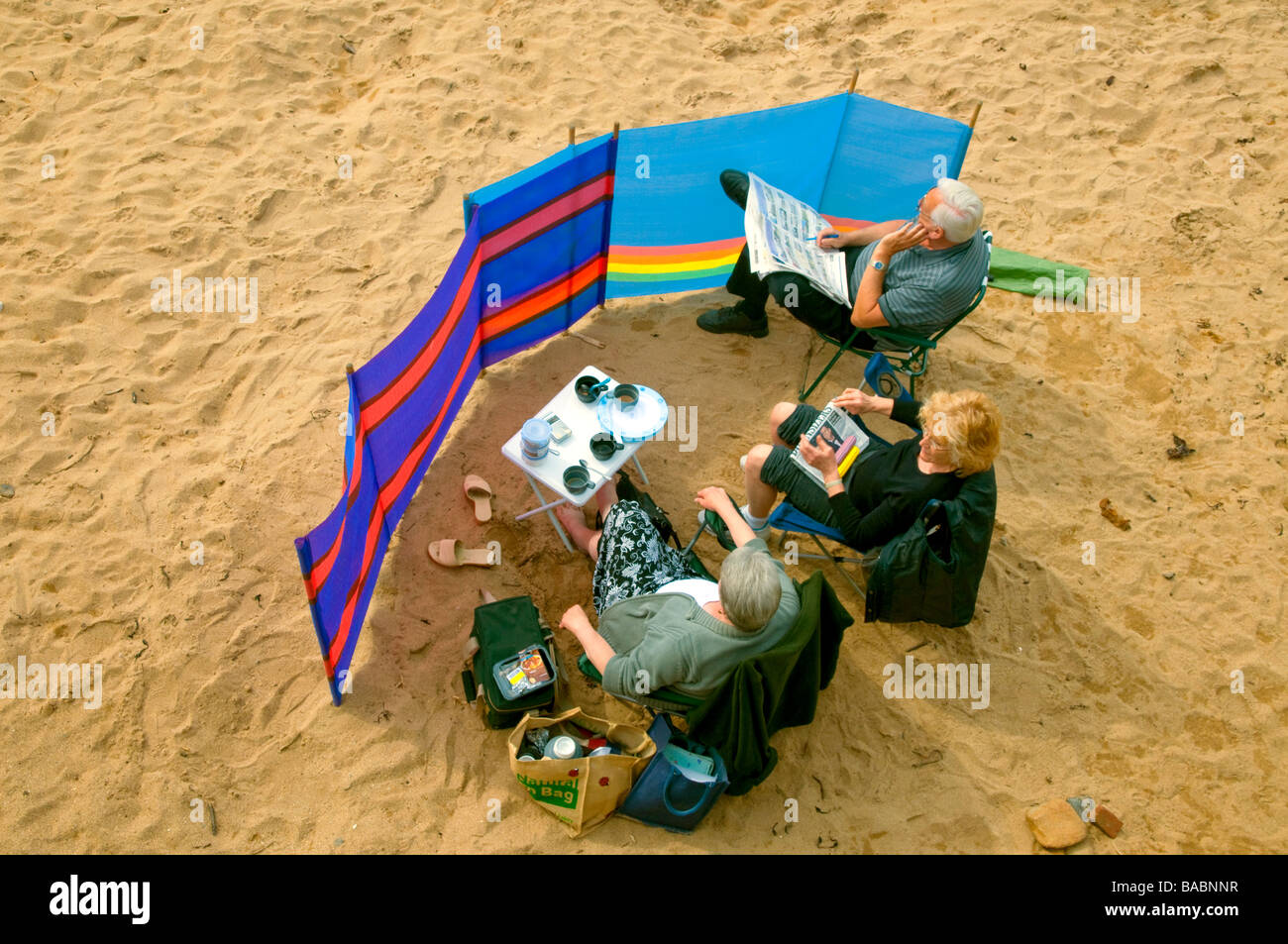 Holiday makers behind a windbreaker  on Hope Cove  beach  Devon - Stock Image