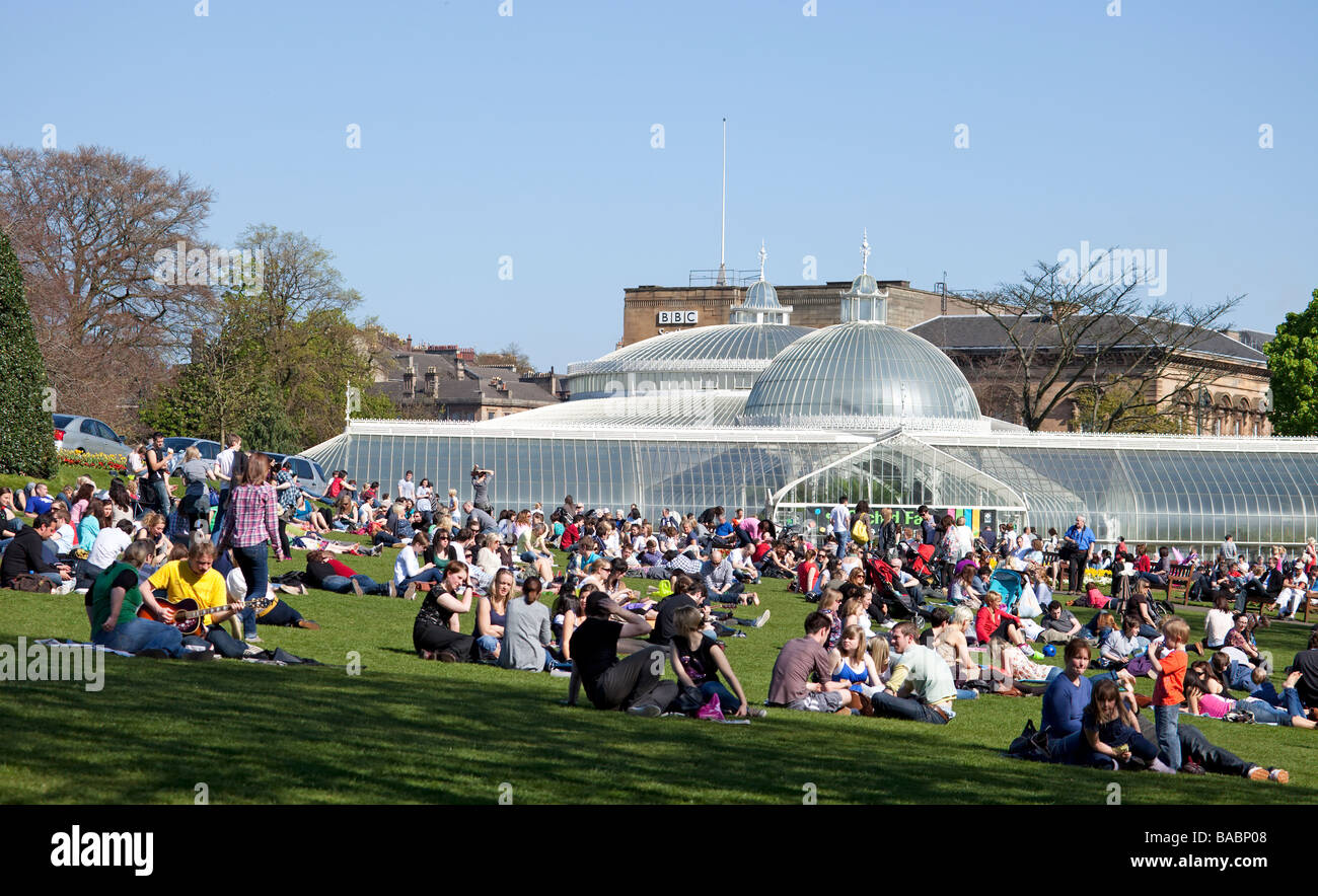 Small groups of people on a lawn in front of the Kibble Palace in Glasgow's Botanic Gardens, enjoying a sunny April Stock Photo