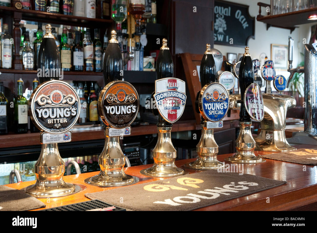 Row of traditional English bitter beer pumps in pub, London England UK - Stock Image