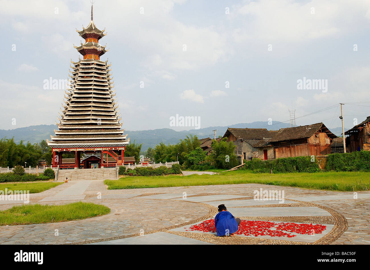China, Guizhou Province, Rongjiang, woman drying red hot chili pepers, Dong Drum Tower in the background Stock Photo