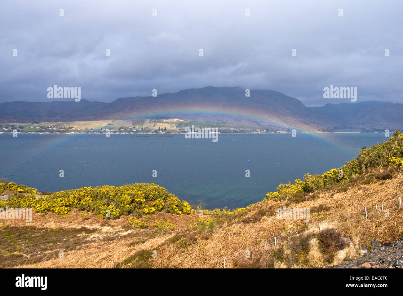 Rainbow over Loch Carron in the West Highlands of Scotland on a showery April day with the settlement of Lochcarron - Stock Image