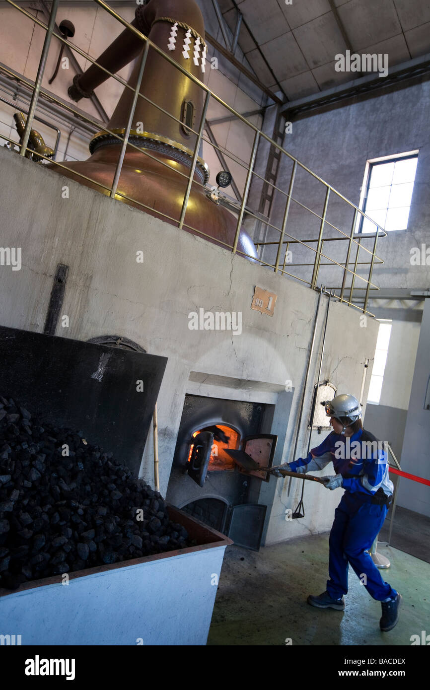 Distillery workers shovel coal into the fires below the Yoichi whisky stills, Nikka whiksy, Yoichi, japan - Stock Image