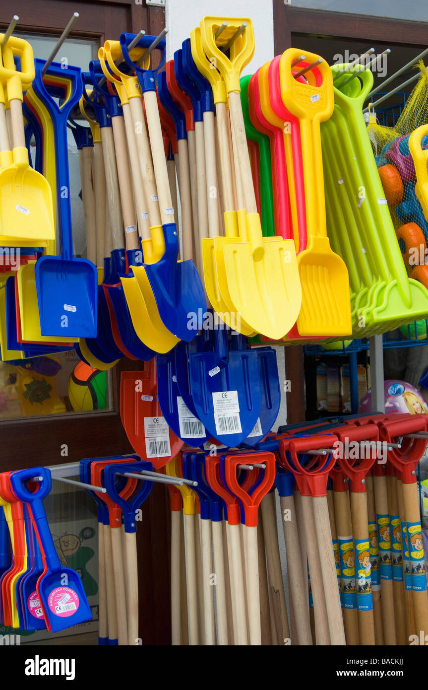 Rows of brightly coloured plastic spades and trowels - Stock Image