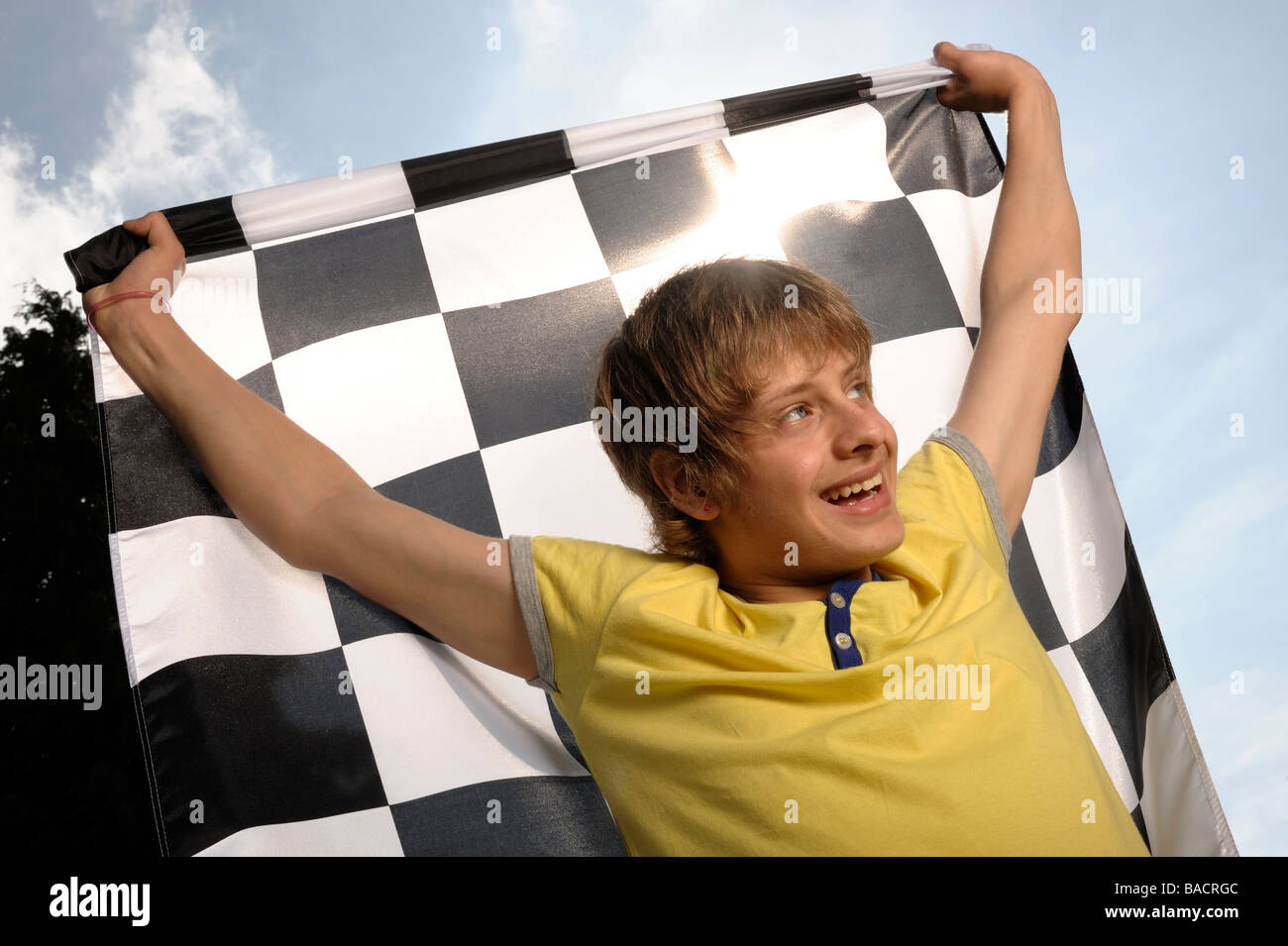 Boy waving a chequered flag - Stock Image
