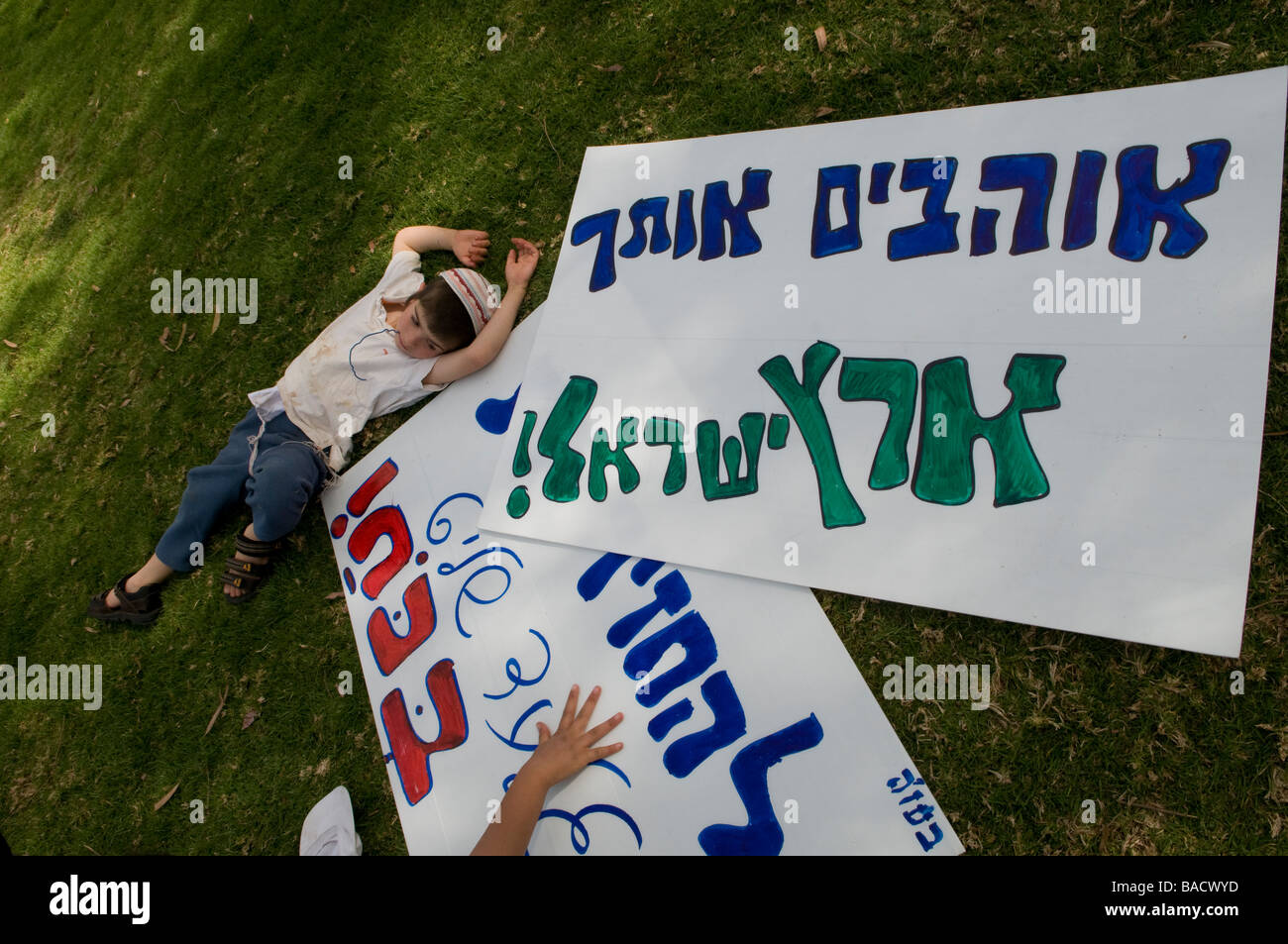 A young Jewish boy lays next to placards during a right wing demonstration in Sderot calling for the resettlement - Stock Image