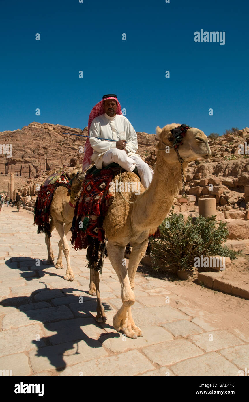 A Jordanian man wearing a typical red and white checked keffiyeh riding a camel in the ancient Nabatean city of Stock Photo