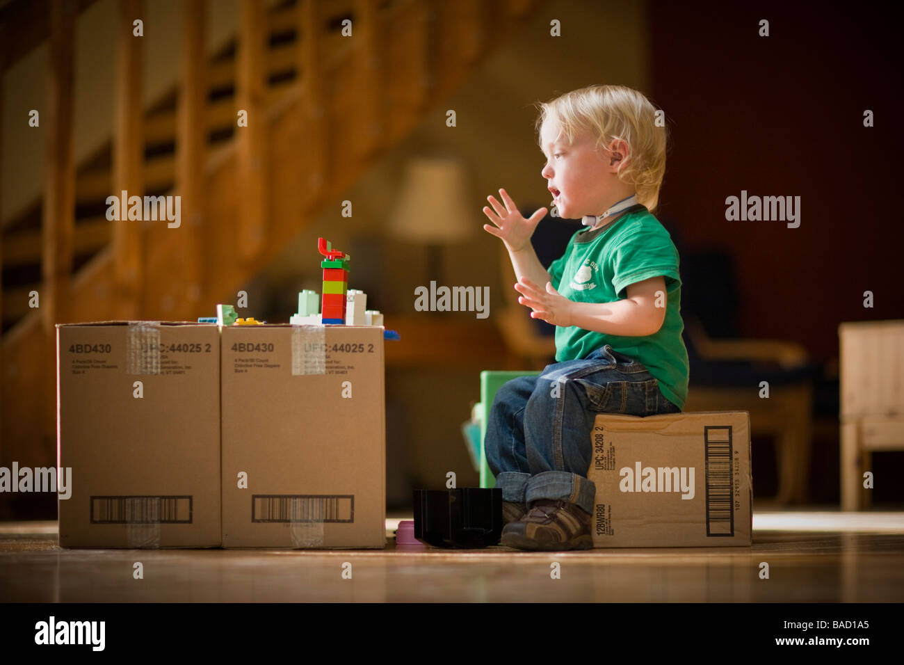 Toddler saying Mom using sign language while playing with toys on cardboard boxes - Stock Image