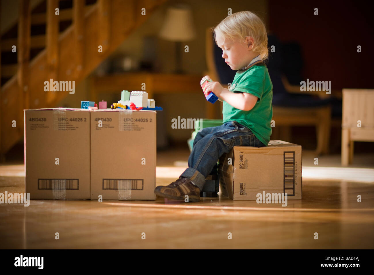Toddler playing with toys on cardboard boxes - Stock Image