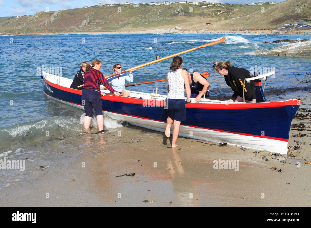 Sennen Cornwall the crew of the Cape Cornwall Pilot Gig boat prepare to launch from the sandy beach at Sennen Cove - Stock Image