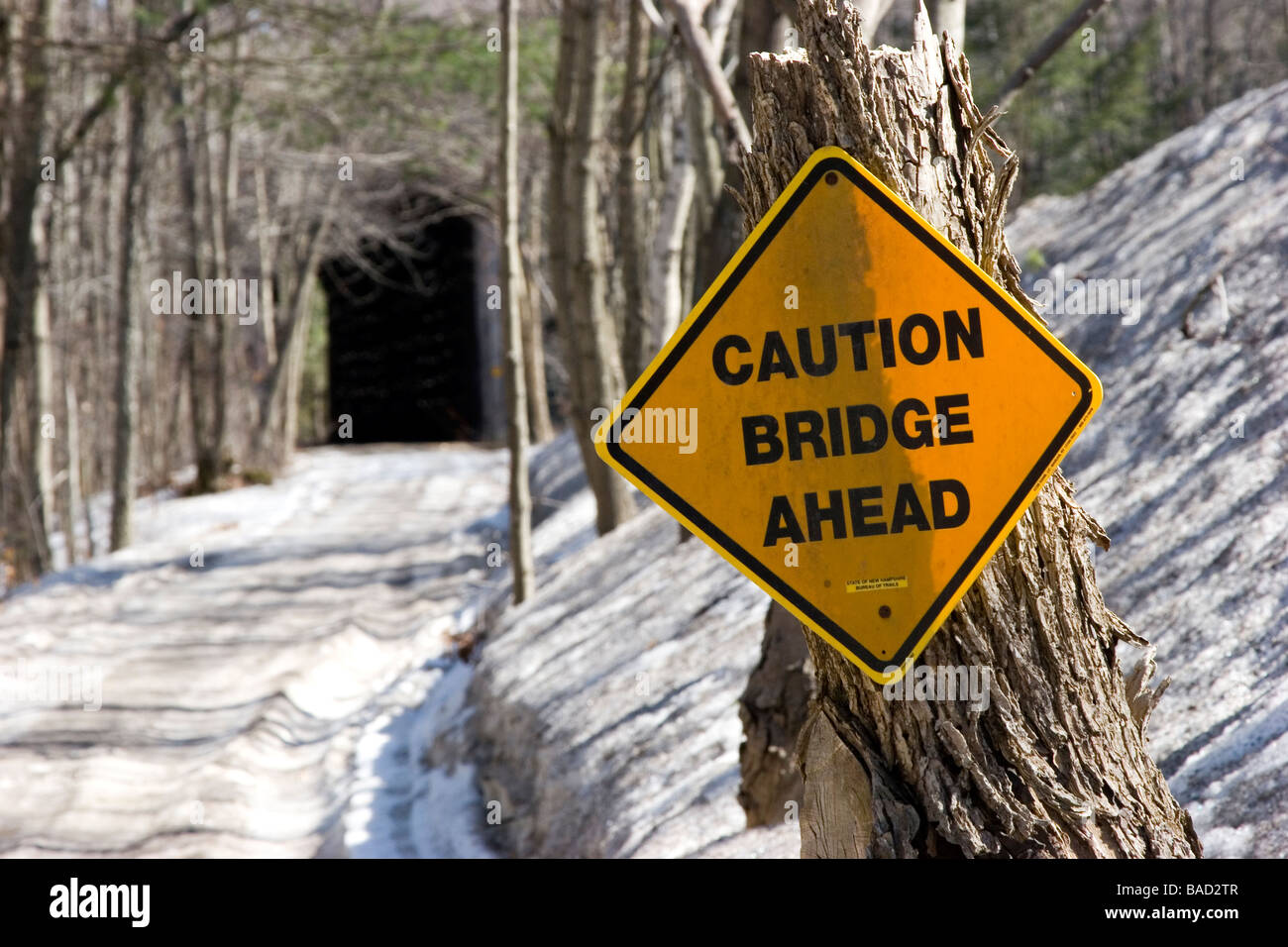 'Caution Bridge Ahead' sign and covered train bridge - Stock Image