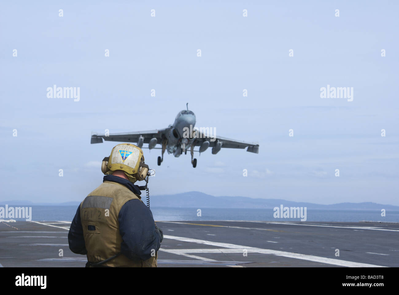 EA 6B Prowler practicing on USS Abraham Lincoln out of homeport, Everett, Washington with Navy crew member standing - Stock Image