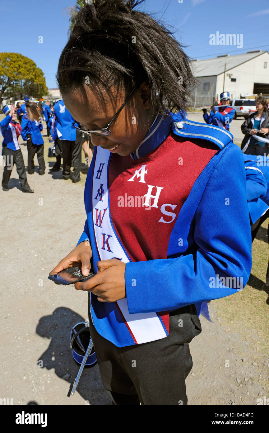 African American high school band member text messaging at Strawberry Festival Plant City Florida - Stock Image