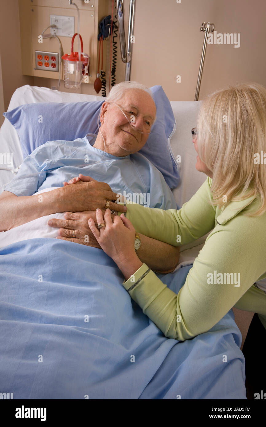 Elderly man and his daughter; Woman sitting by a man's hospital bed - Stock Image