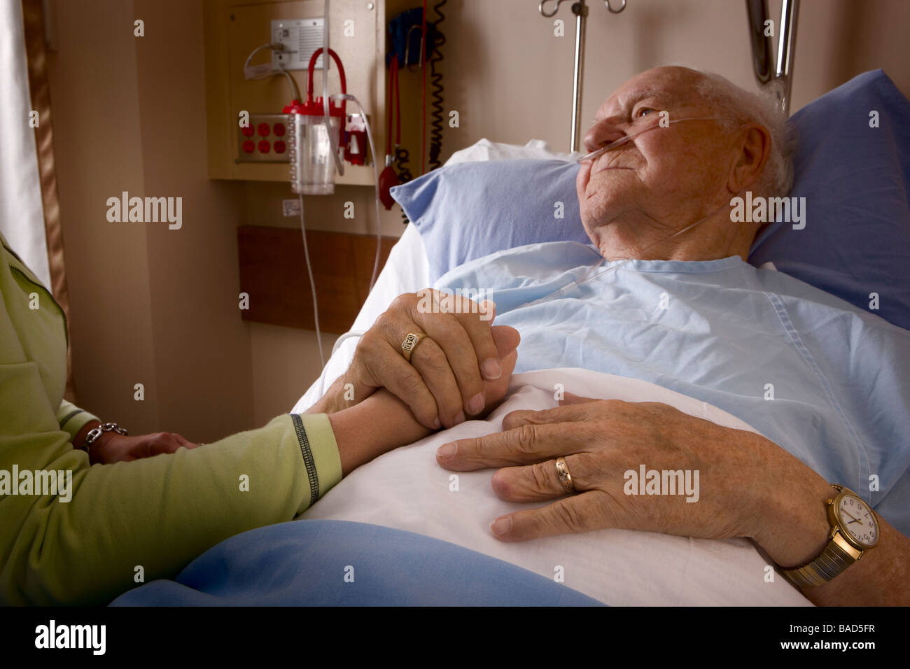 Man in a hospital bed; Man's hand being held by a woman - Stock Image