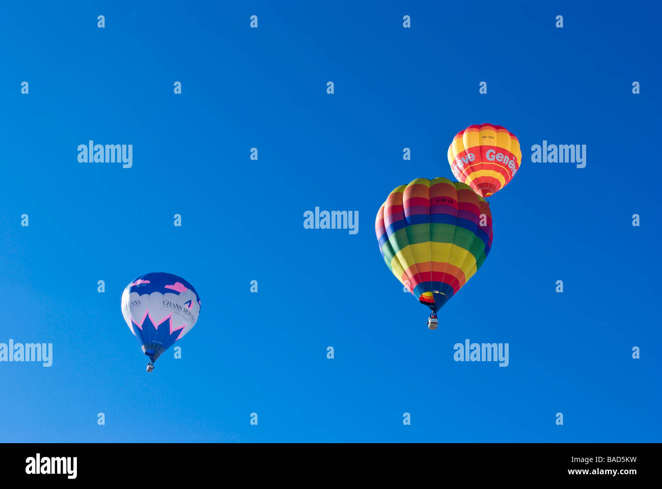 Hot air balloons rising into the clear blue sky at the 2009 Chateau d'Oex international balloon festival / races. Stock Photo
