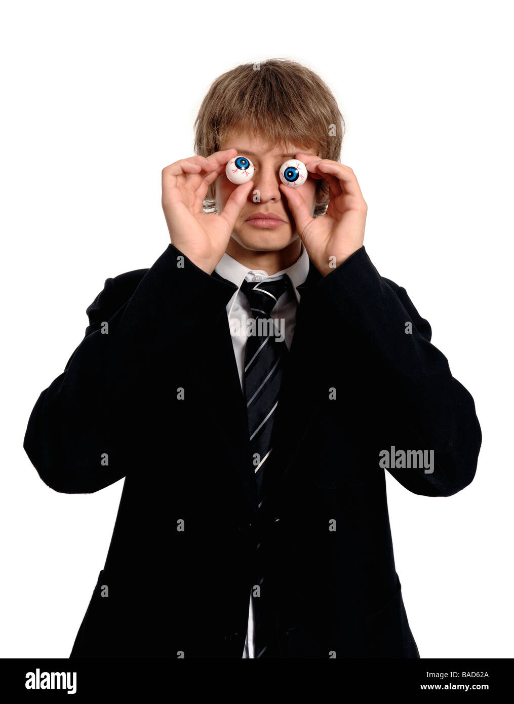 Schoolboy holding joke eyes - Stock Image