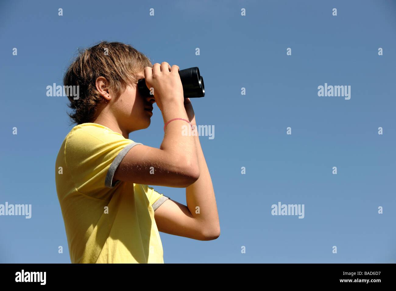 Boy looking through binoculars - Stock Image