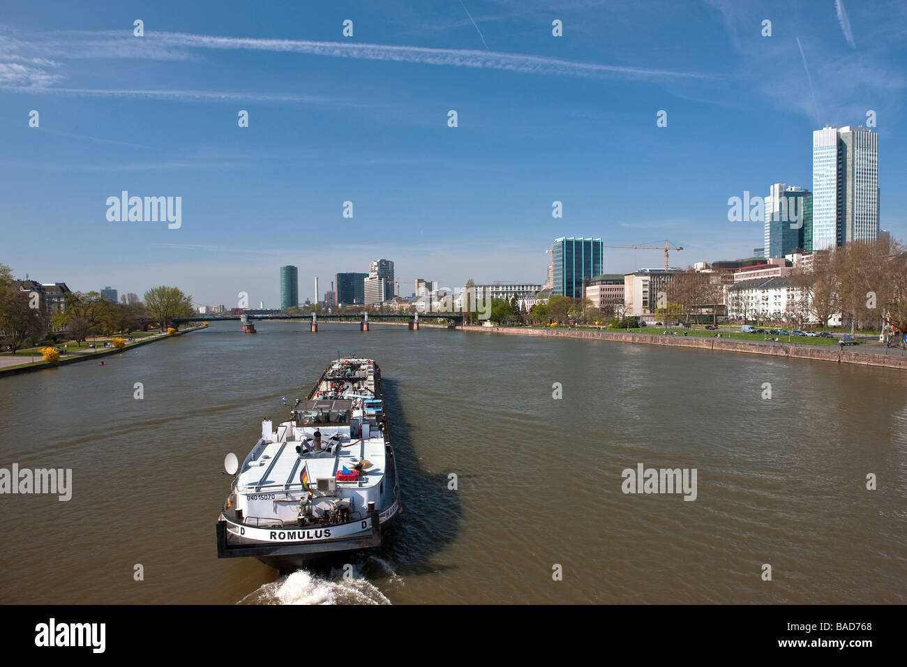 A boat plies the Main River passing through Frankfurt, Germany - Stock Image