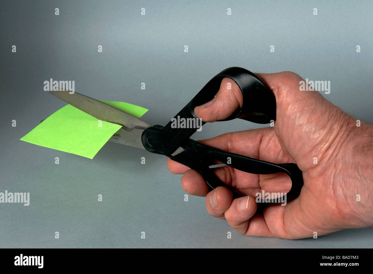 Male hand with scissors cutting green  sticky pad paper - Stock Image