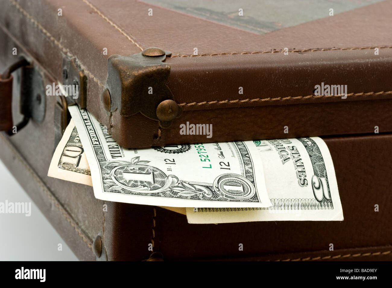 American paper currency hanging out of the corner of an old brown suitcase - Stock Image