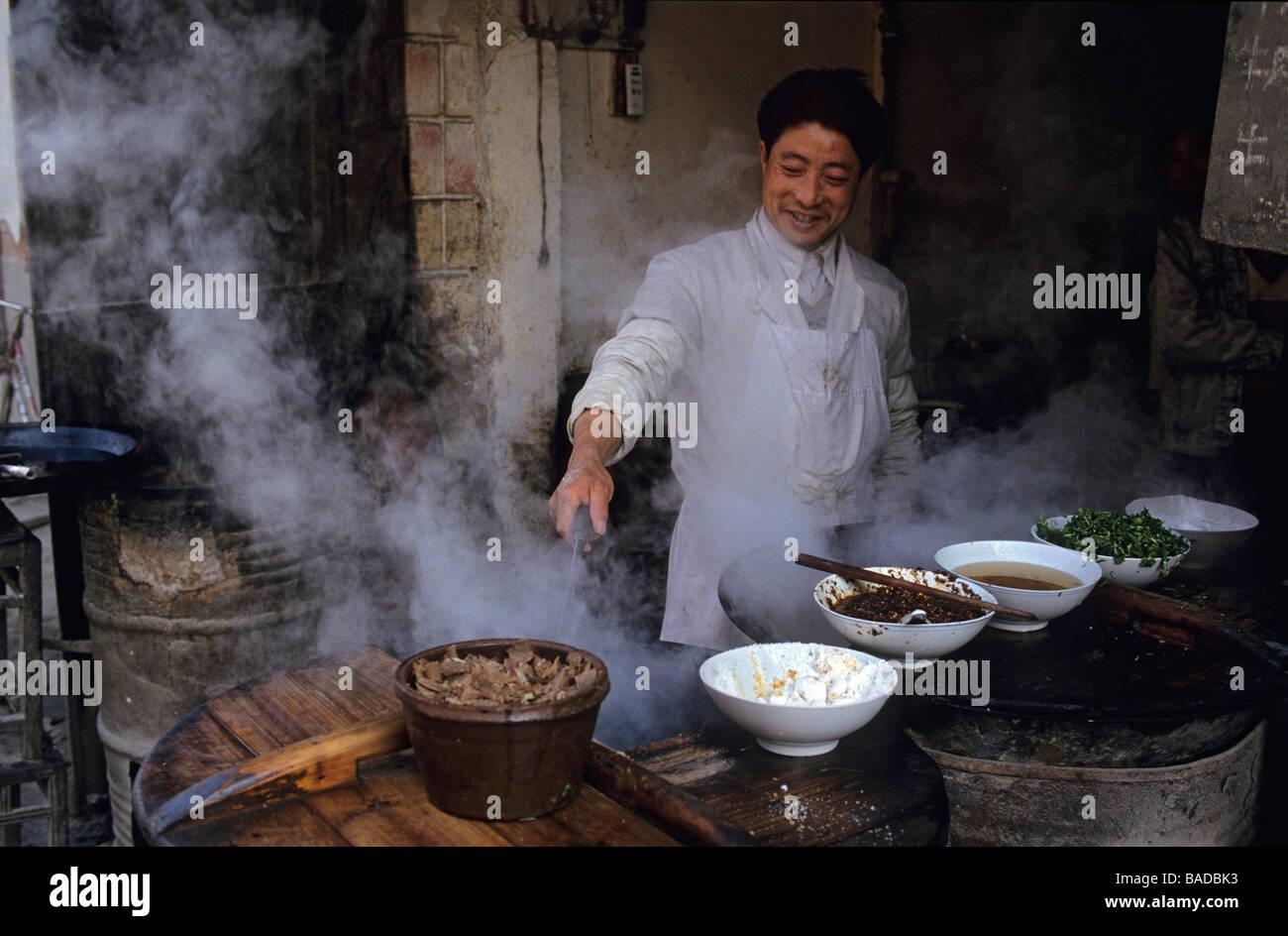 Chine, Jiangsu province, Nanjing, Confucius temple district, man preparing a dish for a street restaurant - Stock Image