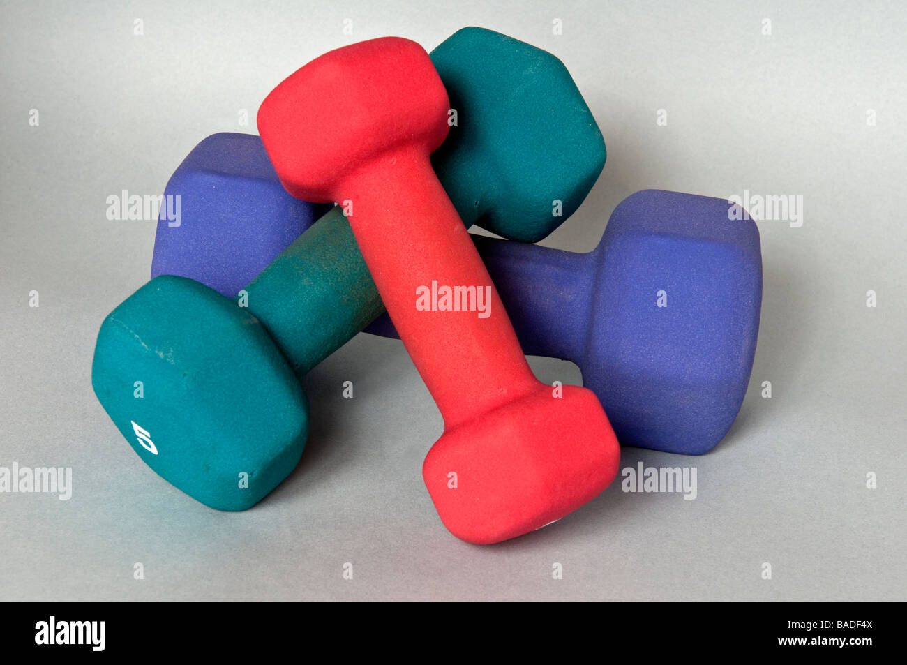 Green blue and red dumbells - Stock Image
