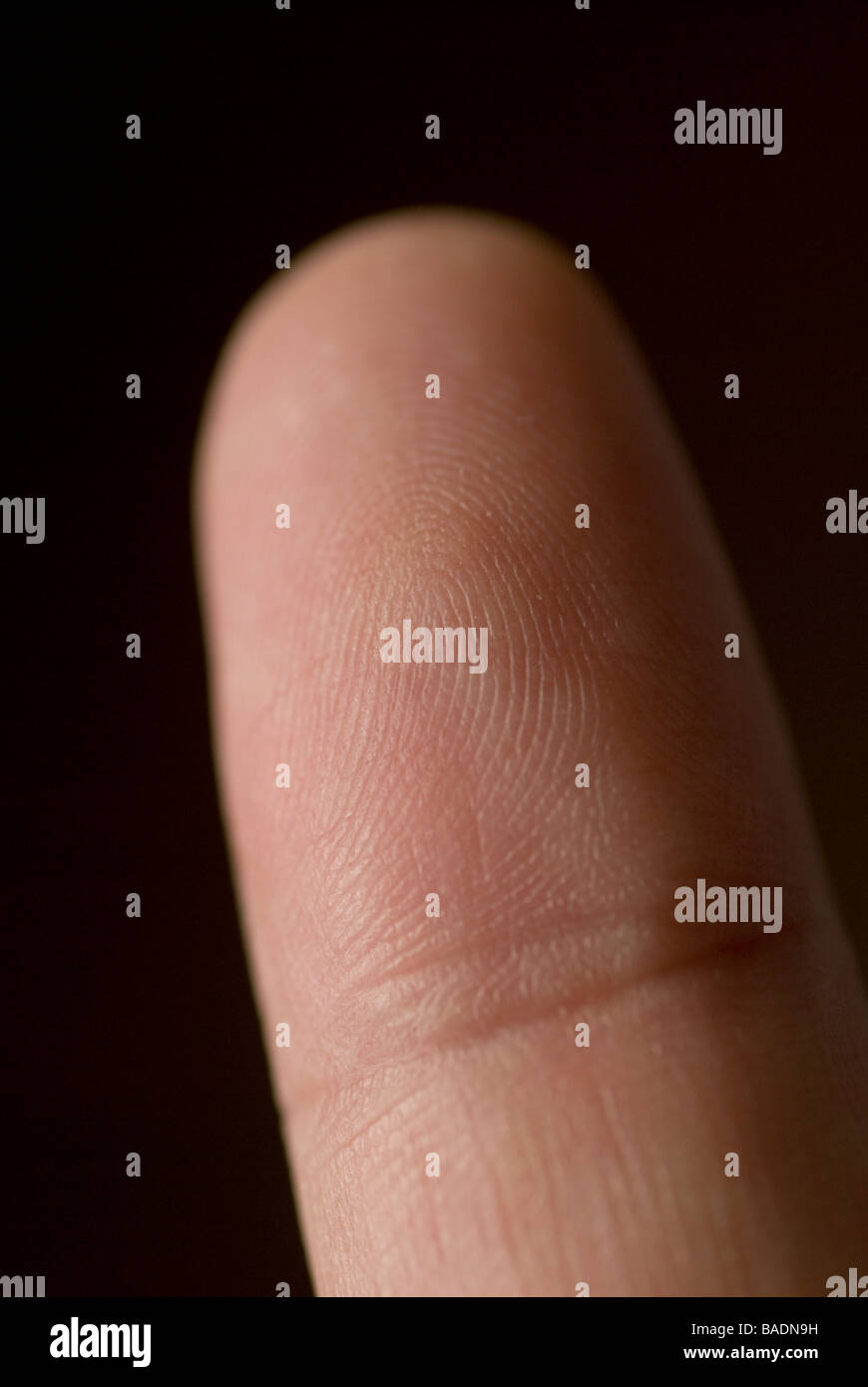 Close up of a man's index finger against a black background Stock Photo