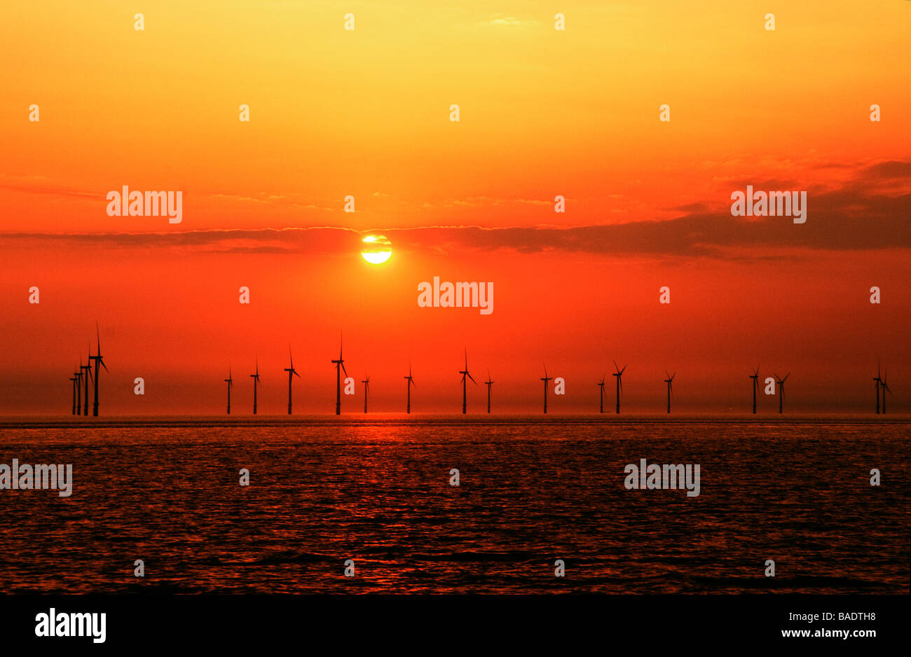 Windfarm with setting sun over sea - Stock Image
