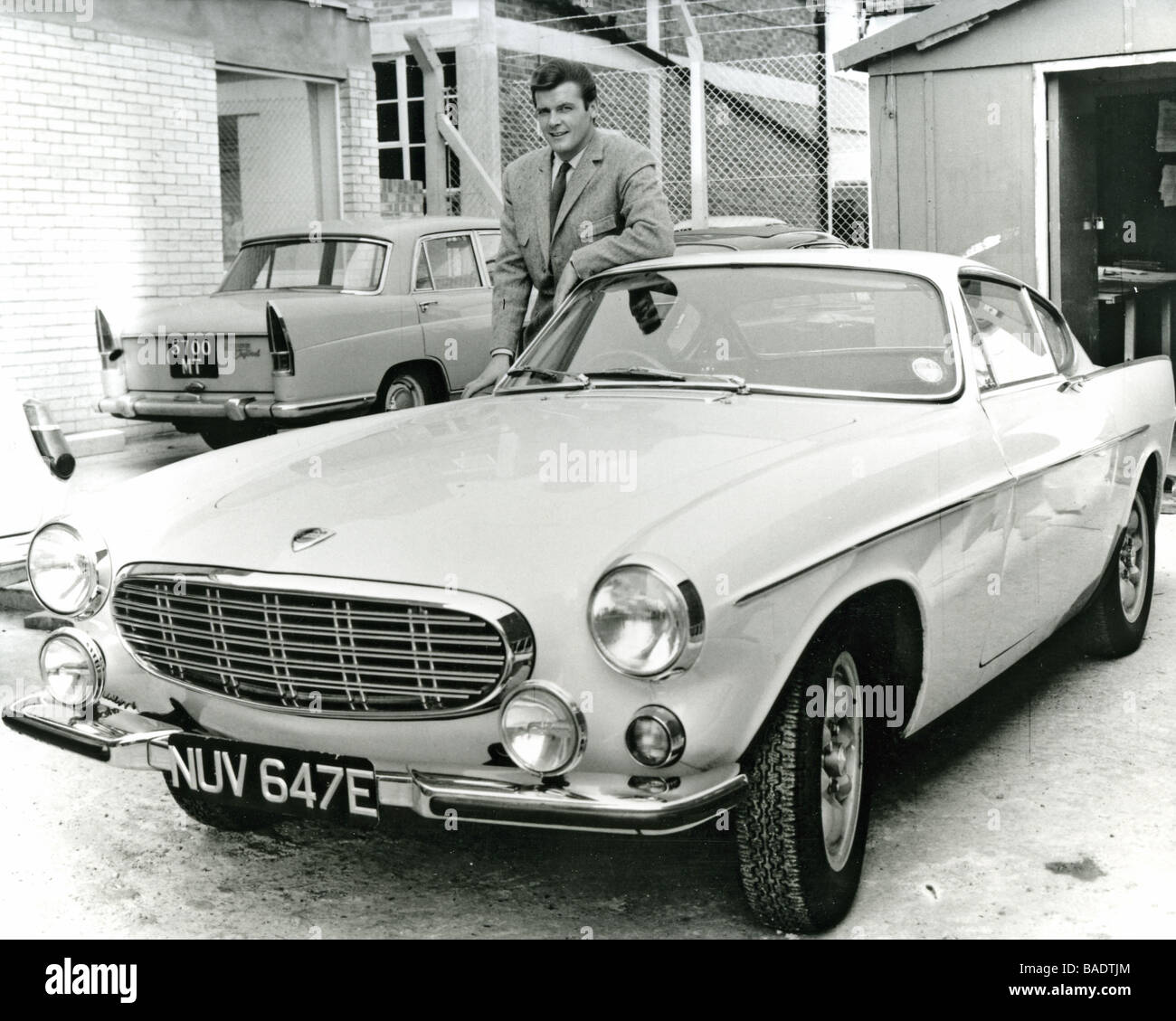 THE SAINT  1960s TV series with Roger Moore seen here with his Volvo P1800 at Elstree Studios - Stock Image
