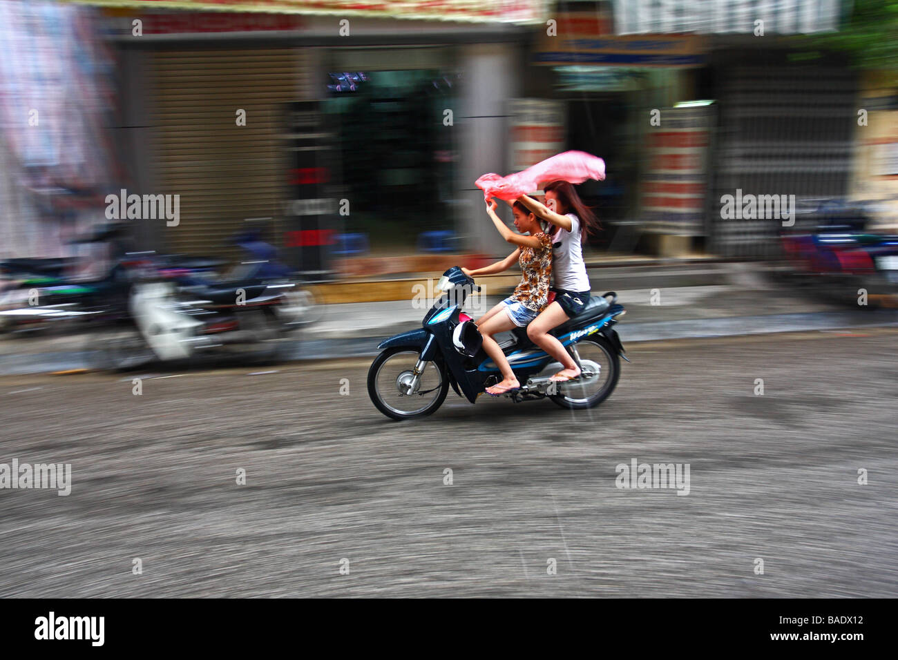 Panning. Street scene. Two, 2 young  girl women riding a scooter under the rain in Hanoi Capital of Vietnam - Stock Image