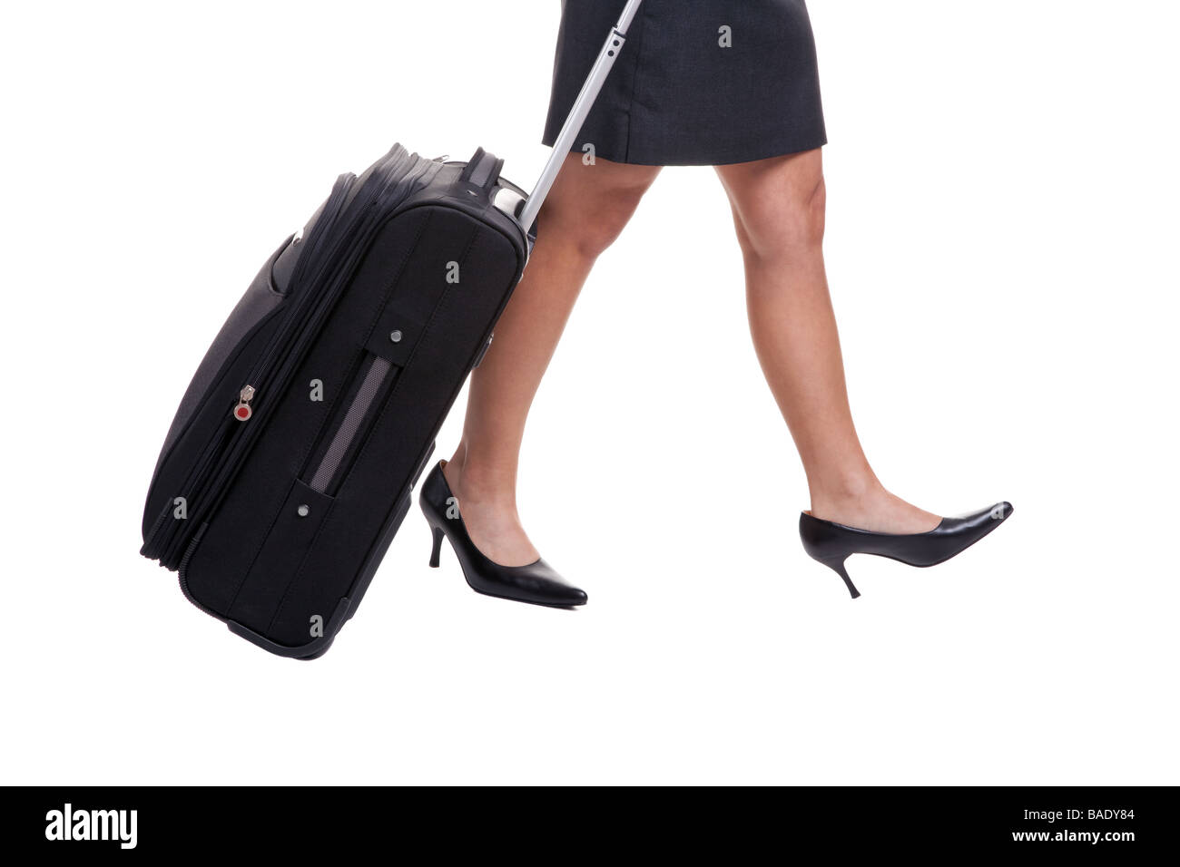 A businesswomans legs in short skirt pulling a suitcase isolated on white background - Stock Image