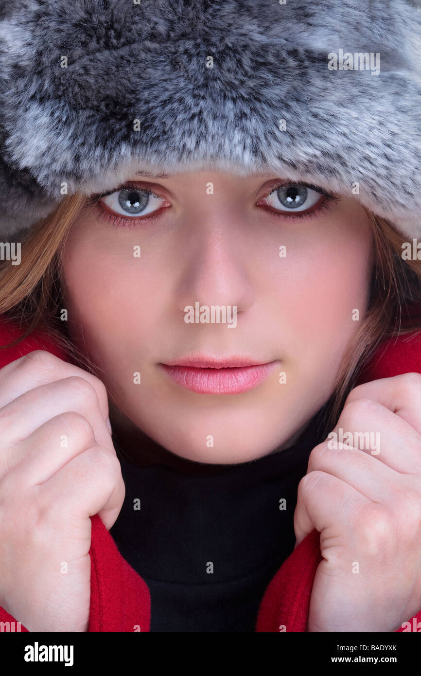 Close up of a woman wearing a fur hat and red coat with the collars pulled up - Stock Image